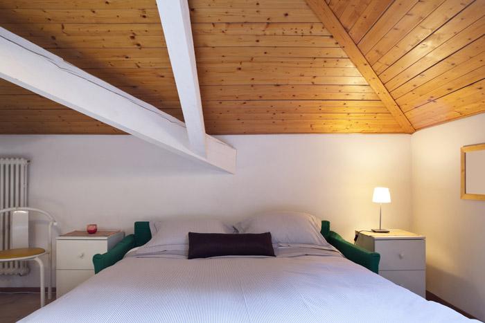Holzverkleidung der Dachschräge mit Balken in Kontrastfarbe